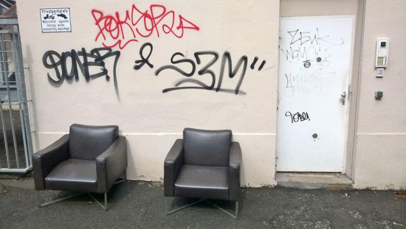 Zwei elegante Ledersessel vor einer Wand mit Graffiti-Tags