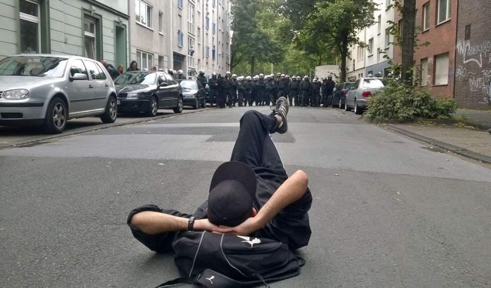 Im Dialog mit der Staatsgewalt. Demonstrant liegr vor Polizeikette auf der Straße.