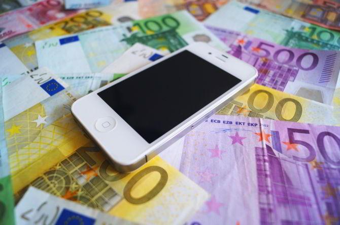Geld und Smartphone auf einem Tisch