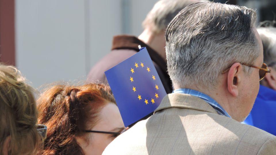 Mann hält kleine EU-Fahne hoch.