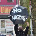 """Demonstrant zeigt einen geöffneten Schrim auf dem """"No Nazis"""" steht."""