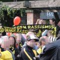 """Bild vom Gegenprotest. Menschen mit BVB Schals auf denen """"Gegen Rassismus"""" steht."""
