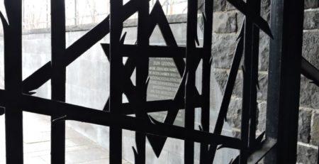 Ein eisernes Tot zu einem Gedenkort in dachau. Ein Davidstern halb verdekct von Eisengittern und dahintr eine Gedenktafel.