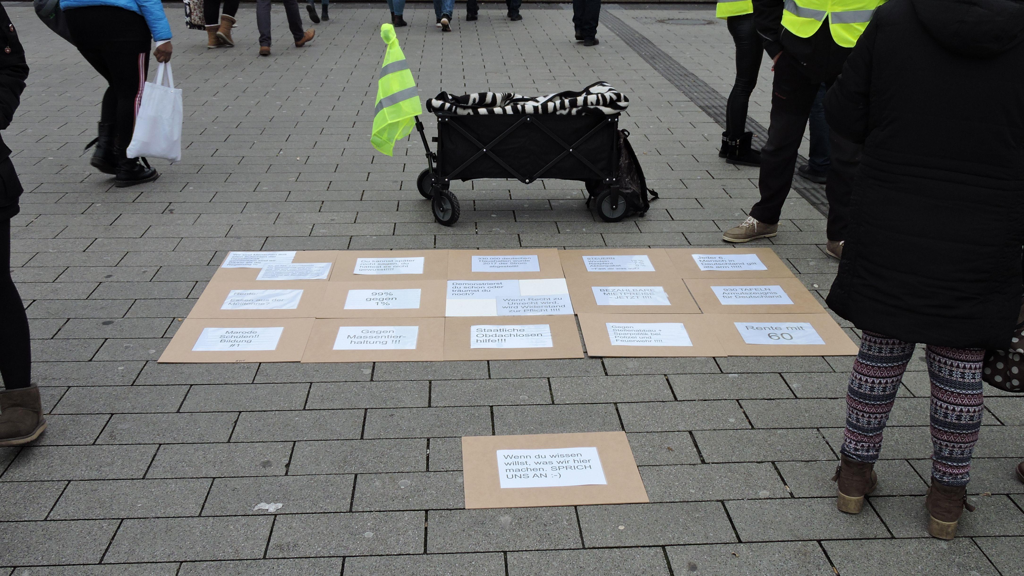Bollerwagen auf dem Platz, davor liegen Pappschilder mit politischen Fortderungen