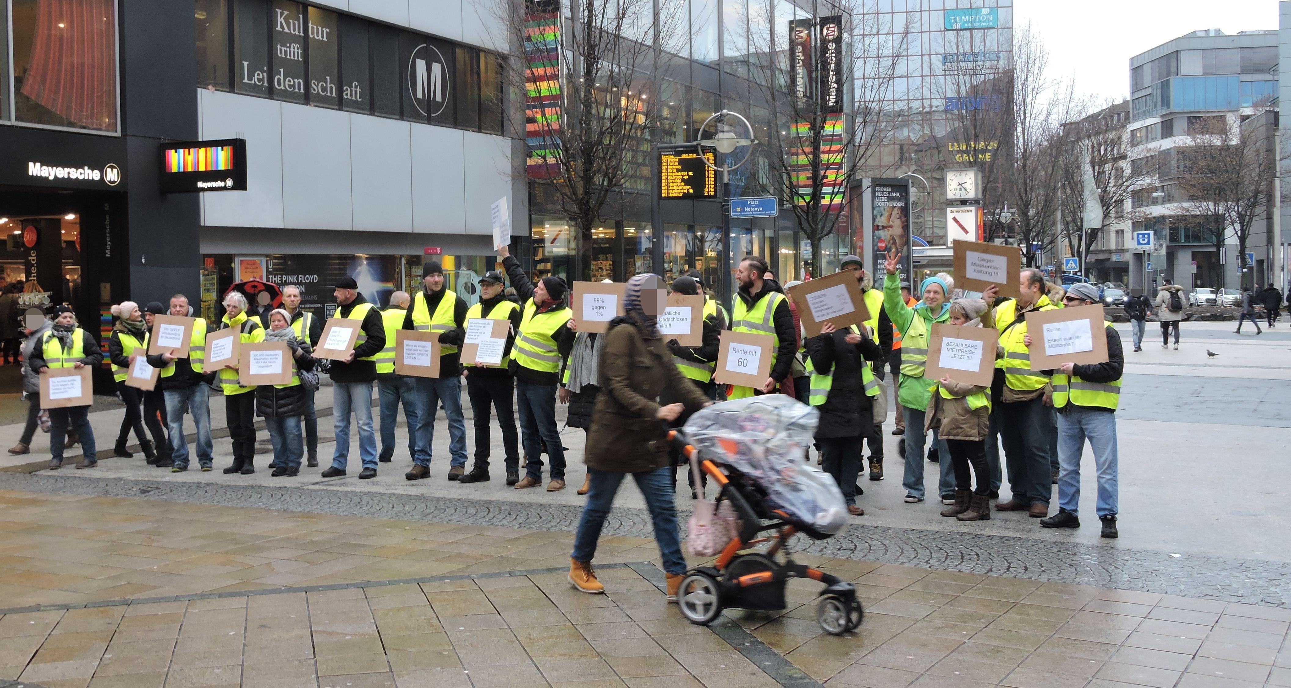Zwischenkundgebung: Menschen halten Schilder hoch