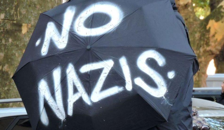 """Bild zeigt einen aufgespanntem Schirm auf dem """"No Nazis"""" steht."""