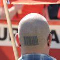 Symbolbilf: Nazi bei einer rechten Demo. Ein Glatzkopf von hinten.