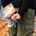 """Bild einer Querdenkenversammlung am 19. Oktober in Dortmund. Ein Mensch hält ein Buch mit dem Titel """"Vom Schatten zum Licht"""" in der Hand."""