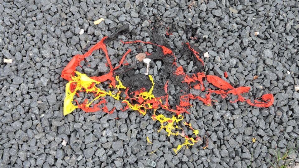 Bild einer verbrannten Deutschlandfahne auf Asphalt.
