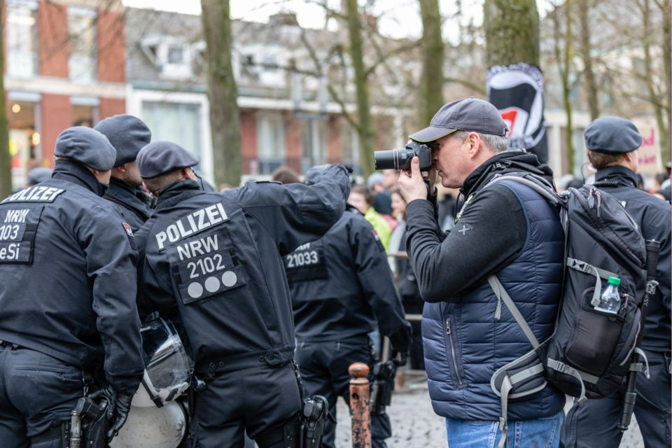 Bild das mich beim Fotografieren auf einer Demonstration zeigt.